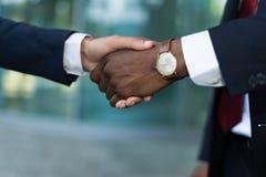 Afrykańskie biznesmena chwiania ręki z caucasian jeden Zdjęcie Stock