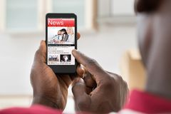 Afrykańskiego mężczyzna Czytelnicza wiadomość Na telefonie komórkowym Obrazy Stock