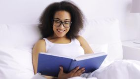 Afrykańskiej kobiety czytelnicza książka w łóżko sypialni w domu zdjęcie wideo