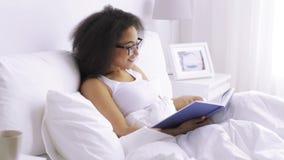 Afrykańskiej kobiety czytelnicza książka w łóżko sypialni w domu zbiory