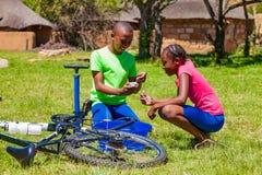 Afryka?scy dzieci za?atwia dziurawienie na rowerze obrazy stock