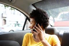 Afrykańska kobieta na tylnym siedzeniu robi rozmowie telefonicza samochód Fotografia Stock