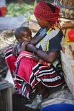 Afryka, Tanzania Zanzibar, Luty, - 2016: Kobieta karmi dziecka na rynku Zdjęcie Royalty Free