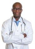 Afrykanin lekarka patrzeje kamerę z krzyżować rękami Fotografia Stock