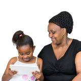 Afrykanin macierzysty i mała córka patrzeje pastylkę wpólnie Obraz Stock