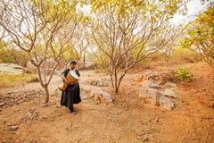 Afrykanin niesie bęben w lesie Obrazy Stock