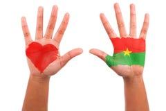 Afrykanin ręki z malującą serca i burkinabe flaga, kocham b Fotografia Stock
