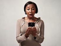 Afrykanin zdziwiona kobieta z smartphone Zdjęcie Royalty Free