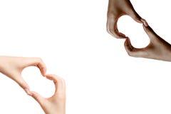 Afrykanina i białej kobiety ` s ręki pokazują symbol serce na białych półdupkach Zdjęcie Royalty Free