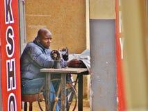 Afrykanina Krawiecki obsiadanie przy Szy Maszynowego czytania gazetą Zdjęcia Stock