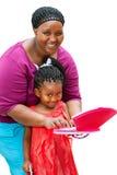 Afrykanina macierzysty pomaga dziecko na laptopie. Zdjęcia Stock