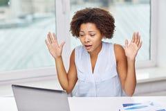 Afrykańska kobieta z laptopem przy biurem Fotografia Stock