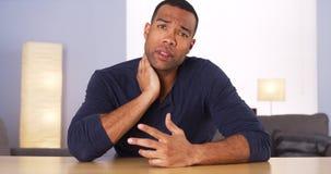 Afrykański mężczyzna wyjaśnia szyja ból kamera Zdjęcia Royalty Free