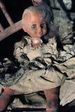 Afschuwelijke poppenzitting op een oude stoel Stock Afbeeldingen