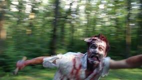 Afschuwelijke zombielooppas in het bos en de vangsten het slachtoffer stock videobeelden