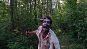 Afschuwelijke zombielooppas in het bos en het zoeken van het slachtoffer stock footage