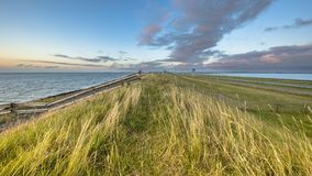 Afsluitdijk dutch dike sunset fence. Afsluitdijk dutch dike with fence motorway and cycling track during  sunset with clouded sky stock image