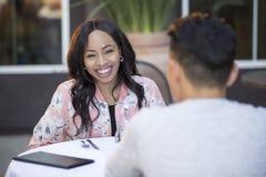 Afspraak tussen onbekende man en vrouw tussen verschillende rassen in Openluchtrestaurant stock foto