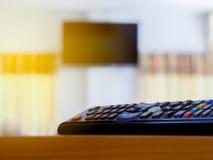 Afstandsbedieningen van TV op de lijst bij de vergaderzaal Gloedlicht Stock Afbeeldingen