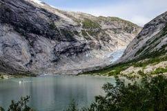 Afstandsmening van de Nigardsbreen-gletsjer met boot op het meer in de voorgrond stock foto's