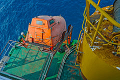 Aft deck of cargo ship. With freefall emergency escape orange lifeboat Royalty Free Stock Image