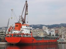 Aft of cargo ship. Aft of red,huge cargo ship in port of city Rijeka at cloudy summer day |crane|derrick Royalty Free Stock Photography