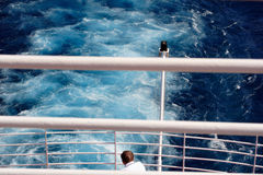Aft View. Man looking over the aft end of a ship on a luxury cruise Stock Photography