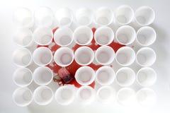 Aftappend theezakje met rode thee tussen rijen van witte plastic koppen, Stock Afbeeldingen