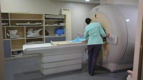 Aftasten medische test /examination in het modern ziekenhuis De machine en de schermen van MRI met arts stock footage