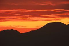 Afterglow of the sunset. And silhouette of the mountains royalty free stock images