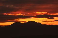 Afterglow of the sunset. And silhouette of the mountains stock photos