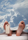 Afterlife. Deceased person covered in a sheet with a blank toe tag. cloudy sky in background stock photography