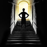 Afterlife, near death experience etc. Filtered image. Concept. Bright light at top of stairs with female figure, challenging royalty free stock photography