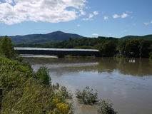 Aftermath of Irene. The Connecticut River and the Cornish-Windsor Covered Bridge, the longest covered bridge in America crosses between New Hampshire and Vermont royalty free stock photography