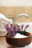 Afternoon Bath. Pretty heather flowers in a bowl of Epsom salts on a bath tub edge ready to bathe Royalty Free Stock Images