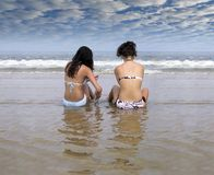 Afternoon at the beach. Two women soak in the sun and water Royalty Free Stock Images