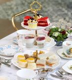 Afternoon British snacks. Afternoon snacks consist of scones, sandwiches, panna cotta, apple crumbles pies, velvet cakes and cupcakes. With hot savory tea stock photography