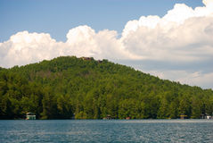 Afternoon Clouds Over the Lake. A mountain at the lake with afternoon clouds building behind it.  Houses can be seen on the very top and at the shoreline Royalty Free Stock Image