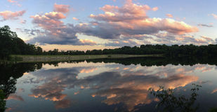Afternoon clouds reflected in still water Stock Images