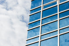 Afternoon cloudy sky reflecting off an office building's curtain Stock Photo