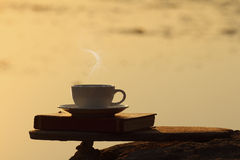 Afternoon coffee cup and book on wooden board with golden light Royalty Free Stock Photos
