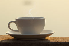 Afternoon coffee cup and book on wooden board with golden light Stock Image