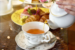 Afternoon english Tea Time. Pouring tea from vintage teapot to the cup, English Tea Time Royalty Free Stock Photos