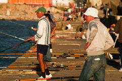 Afternoon Fishing in Montevideo. People on the pier in Montevideo, Uruguay fishing in the late afternoon sun Royalty Free Stock Photos