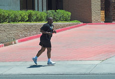 Afternoon Jog. Man running during lunch break mid afternoon in business district Royalty Free Stock Images