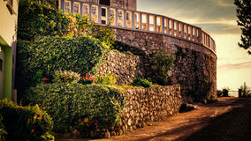 Afternoon light falls on the garden next to the narrow street Royalty Free Stock Photo