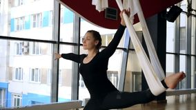 In afternoon near window woman stretches her legs in an air hammock. During yoga female model in black suit leans aside to put limbs in position of gymnastic stock video footage