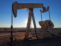 Afternoon at the Oil Well. Pumping hydrocarbons at a desert well on a winter afternoon Royalty Free Stock Images