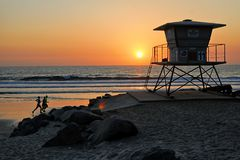 Runners running along the Oceanside beach past a lifeguard tower as the sun sets. Royalty Free Stock Photography