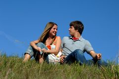 Afternoon outdoors. Two teens sit on grassy hilltop.  Blue skies frame them.  Both are wearing jeans Royalty Free Stock Photo
